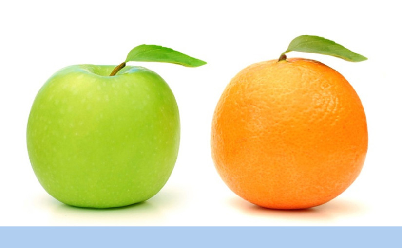 Orange stands out in a line of green apples